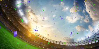 Evening stadium arena soccer field championship win. Wide angle. Evening stadium arena soccer field championship win. Confetti and tinsel . Yellow toning. Wide royalty free stock photography