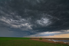 Evening storm over lake in remote wild area. Evening storm and dark clouds over lake in remote eastern European wetland Royalty Free Stock Images