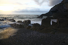 Evening Storm shore. A sombre evening shore with silhouetted jagged rocks and pebble beach Stock Photo