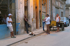 Evening street life of Havana. Cuba, Havana - 08 April, 2016: an evening in Havana, local people chilling out in the shade of houses, tired after a working day Royalty Free Stock Image