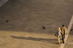 Evening Stroll. A man and woman strolling across a bricked plaza- evening light creating long shadows Stock Photos