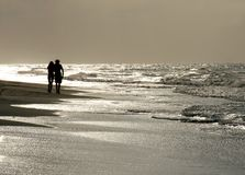 Evening stroll. A couple walking on a beach in the evening sun Royalty Free Stock Images