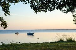 Evening summer view with anchored boat and water scooter Royalty Free Stock Image