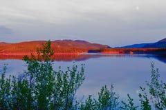 Evening sun glow on calm Twin Lakes Yukon Canada. Red glow of evening sun on boreal forest taiga surrounding calm water surface of Lake Twin Lake near Carmacks stock photo