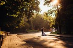 Evening sun illuminates the street where wedding couple kisses.  Stock Images