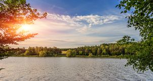 Evening sun over river. trees in the forest under sunshine at unset. colorful sky. Evening sun over river. trees in the forest under sunshine at sunset royalty free stock photography