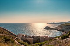 Evening sun on lighthouse at entrance to Bonifacio port stock image
