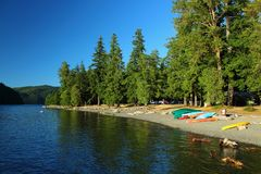Beach and Boats at Crescent Lake, Olympic National Park, Washington. Evening sun shines on colourful canoes sitting on the pebble beach near Lake Crescent Lodge Stock Photography
