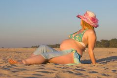 Evening sunburn. The pregnant woman on a beach. The most useful sunburn,-evening (especially for pregnant women Stock Images
