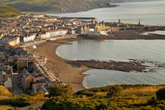 Evening sunlight on Aberystwyth. The evening sun lights up Aberystwyth in Wales, Uk, photographed from high above the town on Constitution Hill Stock Image