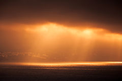 Evening sunlight goes through dark cloudy sky Royalty Free Stock Images