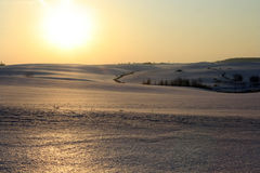 The evening sunset. Sun reflected in thawed winter snow Royalty Free Stock Images