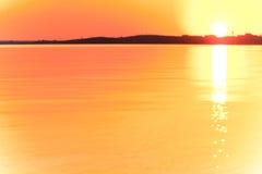 Evening sunset with beautiful sun glare on the water. Uncomplicated evening sunset with beautiful sun glare on the water. A strip of coast on the horizon dark Royalty Free Stock Photography