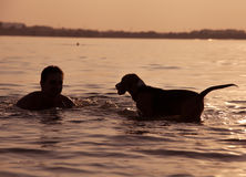 Evening sunset: boy with puppy in waves Royalty Free Stock Photography