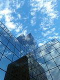 A modern building lined with glass. Evening, sunset, cloudy sky in reflection.  a modern building lined with glass Royalty Free Stock Photo