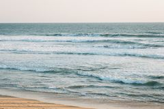 Evening sunset light on the beach and waves in the Pacific Ocean in Huntington Beach, Orange County, California.  stock image