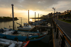Evening sunset over boats at a pier near the popular Old Street area of Tamsui District. New Taipei City, Taiwan - August 3, 2017 - The sun sets over the Tamsui Stock Photos
