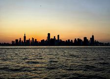 Evening sunset over Chicago silhouettes the skyline, as seen from Lake Michigan. Which is glowing with orange sunlight Stock Photography