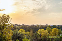 Evening sunset over the roofs of suburban houses. Autumn landscape in backlight sunlight. Royalty Free Stock Photos