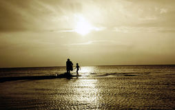 An evening swim. A child is swiming in the sea with his mother. Nice evening sun. Sepia mode Royalty Free Stock Images