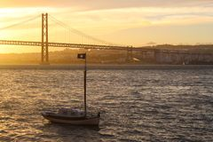 Evening on the Tagus River. Golden late afternoon light illuminates the 25th of April Bridge and a small boat on the Tagus River. Lisbon, Portugal Stock Photos