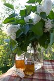 Evening tea party on the balcony. Glasses with tea and a bouquet of lilac. Evening summer tea. Cold refreshing drinks at the end of the day Royalty Free Stock Photography