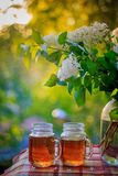 Evening tea party on the balcony. Glasses with tea and a bouquet of lilac. Evening summer tea stock photos