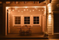 In the evening, the terrace of a wooden house is lit with luxury retro light bulbs, a wooden table is served for a. Romantic dinner for two, dishes, flowers royalty free stock image