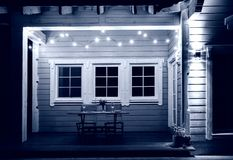 In the evening, the terrace of a wooden house is lit with luxury retro light bulbs, a wooden table is served for a. Romantic dinner for two, dishes, flowers stock images