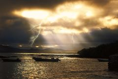 Evening thunderstorm at seashore of Galapagos. Evening thunderstorm with light beams at the coast of a Galapagos Island, Ecuador Stock Photo