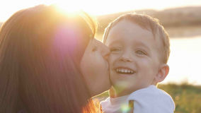 At the evening time before the sunset, baby feeling happy and smiles with her mother in the garden Stock Photo