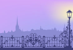 Evening town. Evening city street with streetlight and wrought fence copy space vector background royalty free illustration