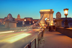 Evening traffic on Suspension Bridge in Budapest, Hungary. Evening traffic and passing pedestrians on Suspension Bridge in Budapest, Hungary, toned image Stock Photo