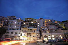 Evening traffic in Tripoli. Street traffic and blurred pedestrians in Tripoli, Lebanon. Seen during the winter evening with the car lights and the houses built Stock Image