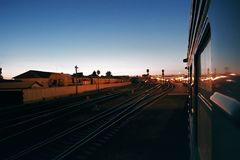 Evening train enters railway station, train arrival Royalty Free Stock Image