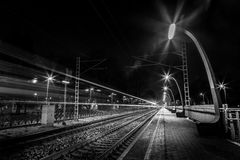 Evening train passing train station Royalty Free Stock Image