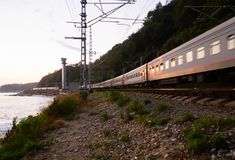 Evening train from Sochi goes along the Black Sea coast Stock Photos