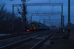 A locomotive with five cars is on the railroad tracks in the evening. royalty free stock photography