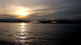 Evening trip on Inle Lake, Myanmar. Evening trip on Inle Lake with a view on cloudy sunset sky, ripples on water surface and fast floating kayaks, Nyanmar stock video footage