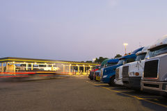 Evening truck stop lights of number of trucks in parking Stock Photo