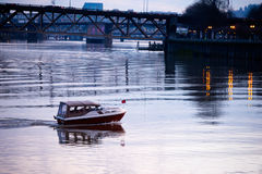Evening urban river with boat on water bridges over water and wa Royalty Free Stock Photo
