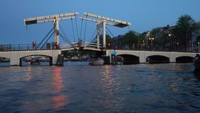 Evening view of Amsterdam. Canals, boat passing under bridge decorated by illumination, architecture and street lights. stock video footage