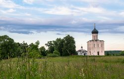 Evening view through Bogolubovo meadow towards the Church of the Intercession of the Holy Virgin on the Nerl River. Bogolyubovo meadow has rich and variety Royalty Free Stock Image