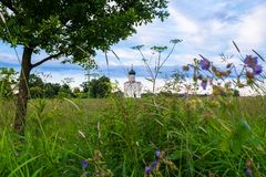 Evening view through Bogolubovo meadow towards the Church of the Intercession of the Holy Virgin on the Nerl River. stock image