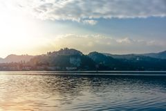 Evening view of the city from the lake. View of the city waterfront and mountains stock photo