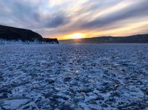 Evening view. Cracks on the surface of the blue ice. Frozen lake Baikal in winter mountains. It is snowing. The hills of pines. Ca