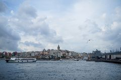 Evening view of Galata tower district, bridge with people fishing and Bosporus sea water with boats, seagulls and cloudy sky. Istanbul, Turkey - May 26, 2018 Stock Images