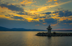 Evening view of lighthouse at sunset. Panoramic evening view of lighthouse at sunset with dramatic clouds in sozopol, bulgaria Royalty Free Stock Photo