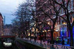 Evening view of Manchester. MANCHESTER, UNITED KINGDOM - 5 March, 2016: Evening view of a lit up street and canal in the city of Manchester in the north of Royalty Free Stock Photos