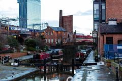 Evening view of Manchester. MANCHESTER, UNITED KINGDOM - 5 March, 2016: An evening view of a river canal in Manchester with boats, bridges and a passing train Stock Image